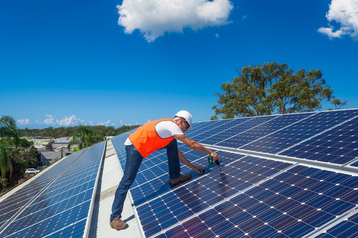 A worker installing rooftop solar panels.