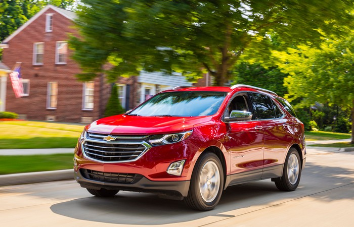A red 2018 Chevrolet Equinox crossover SUV on a suburban street.