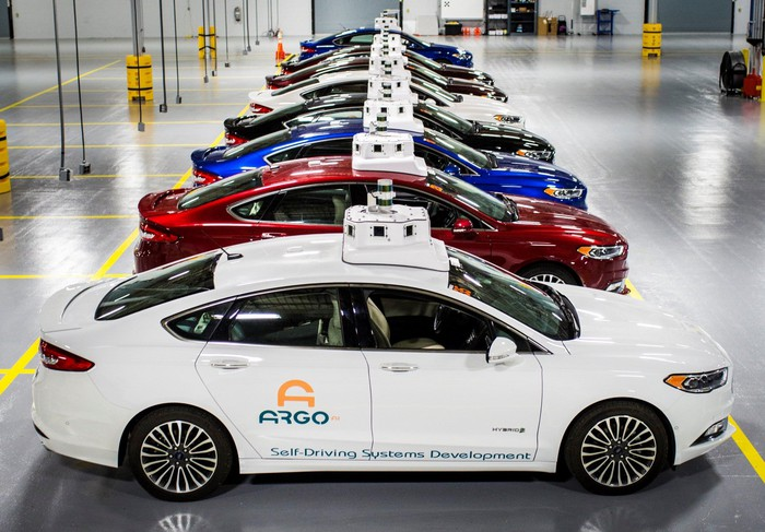 A row of Ford Fusion Hybrid sedans with Argo AI logos and visible self-driving sensor hardware, parked in a garage.