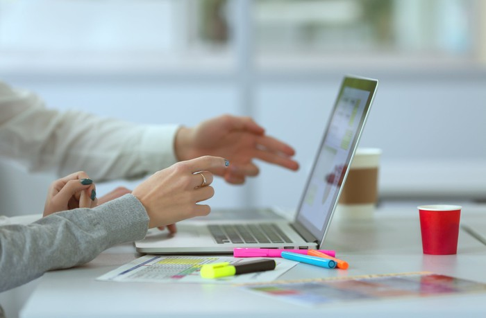 Hands pointed toward laptop screen with papers and highlighters next to it