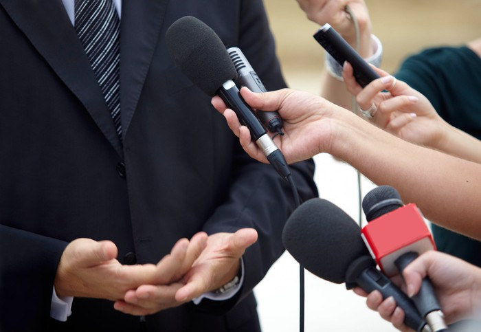 People pointing microphones at a man in a suit