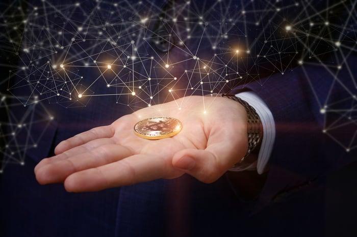 Hand holding a golden coin with bitcoin logo.
