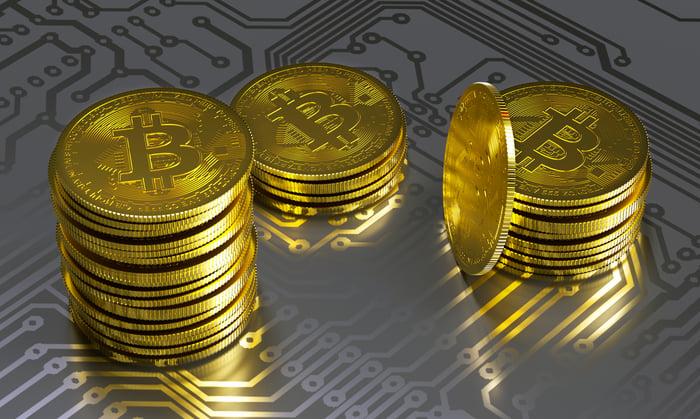 Stacks of physical gold bitcoin atop a gray circuit board.