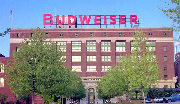 The front of a Budweiser factory. The building is made of brick, has glass windows, and is five stories tall.