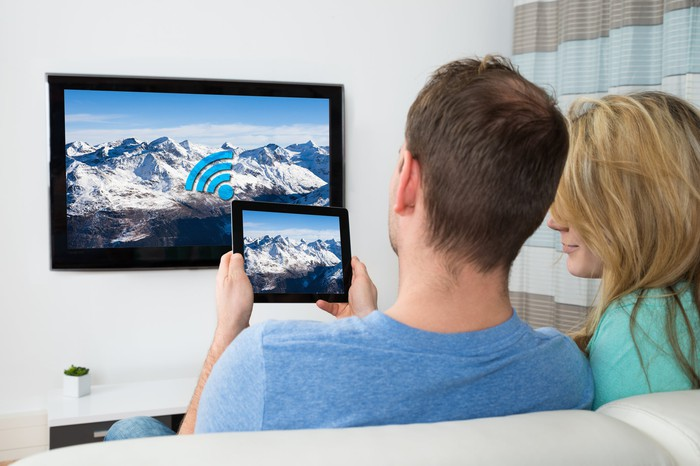 young couple watching TV and holding up a tablet with the same screen image in front of them.