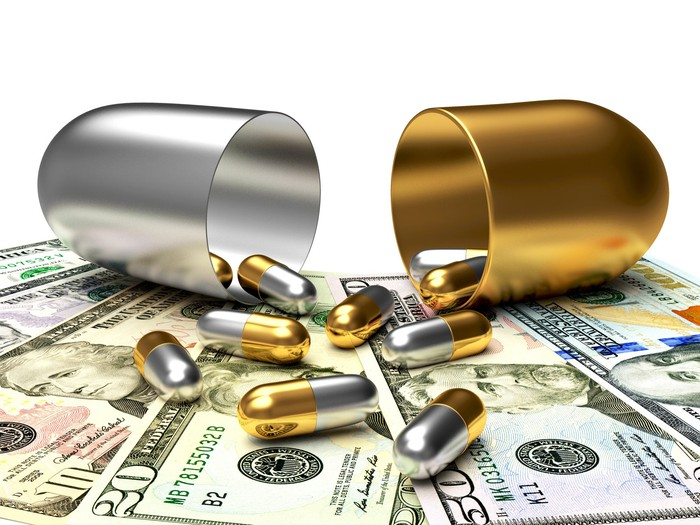 Silver and gold pills spill out of a large silver and gold capsule onto a pile of paper currency.