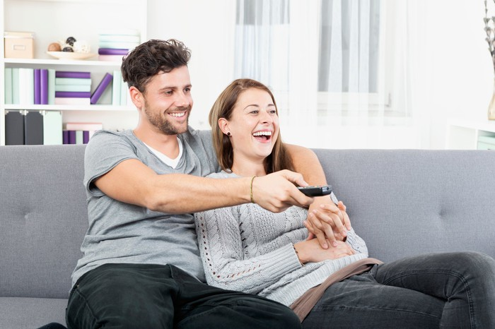 Couple sitting on couch smiling watching TV with man holding the remote.