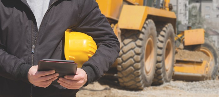 A construction worker with a tablet standing in front of heavy equipment.
