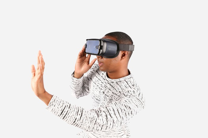 Man wearing Gear VR on his head and holding his hand out