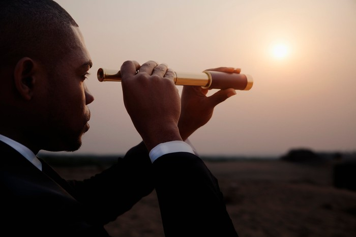 man in business suit looks through a telescope to a hazy horizon as the sun sets.