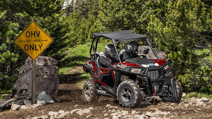 Two helmeted riders in a Polaris Industries RZR 900 on a wooded trail.