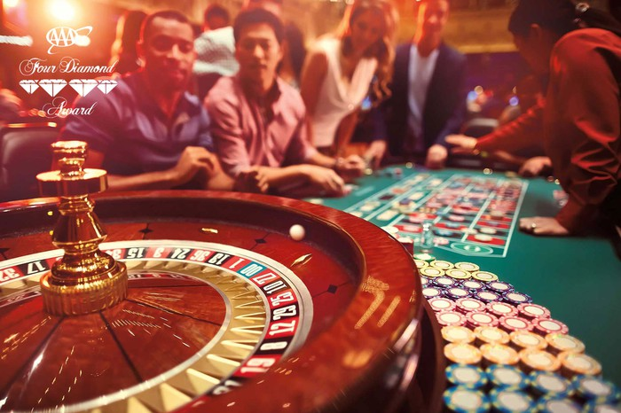 People around a gaming table playing roulette.