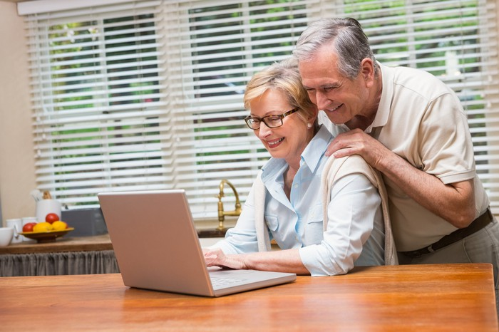 Man and woman in their 60s looking at laptop