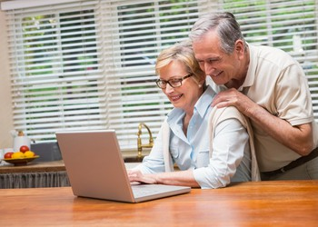 Couple in their 60s looking at PC