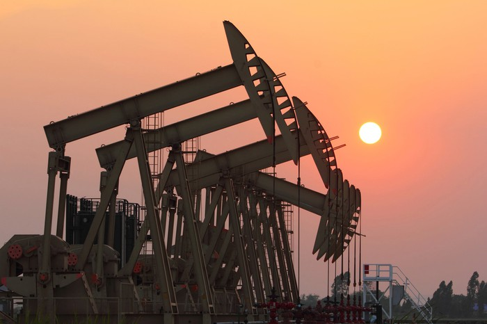 A group of oil pumps with the sun setting.