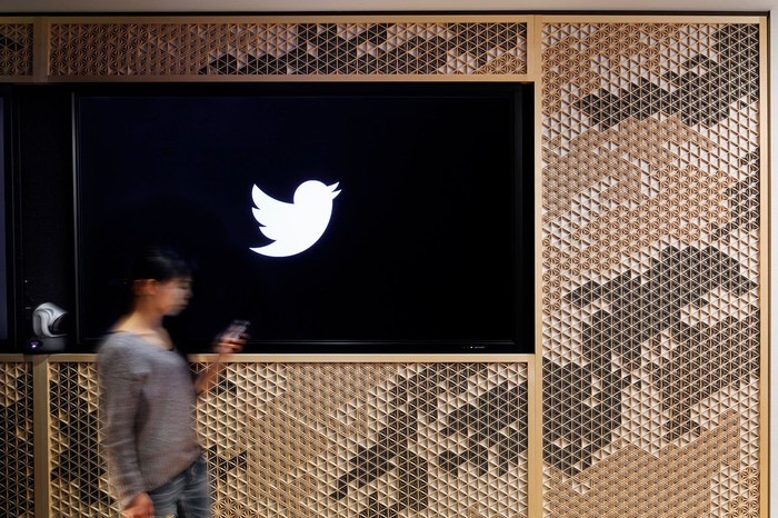 Woman walking by a black and white banner with the Twitter logo