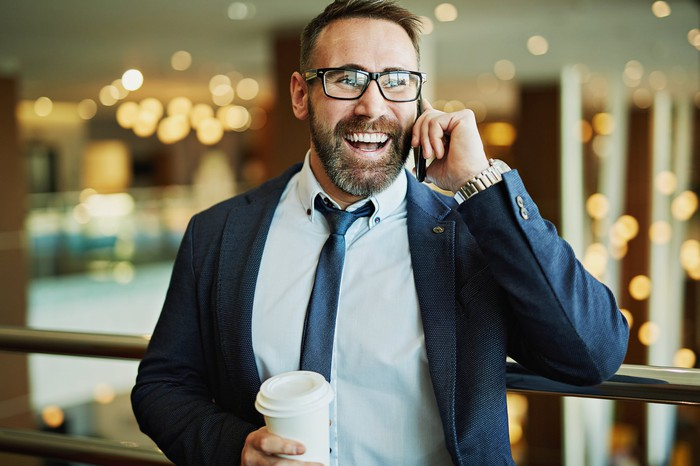 A smiling man in jacket and tie speaks on the phone, while holding a covered white beverage cup in the other hand.