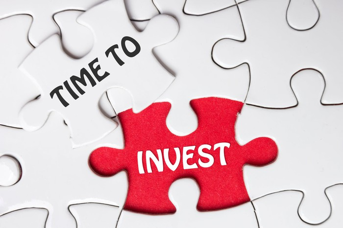 """Many white jigsaw-puzzle pieces and one red one; two together say """"time to invest"""""""