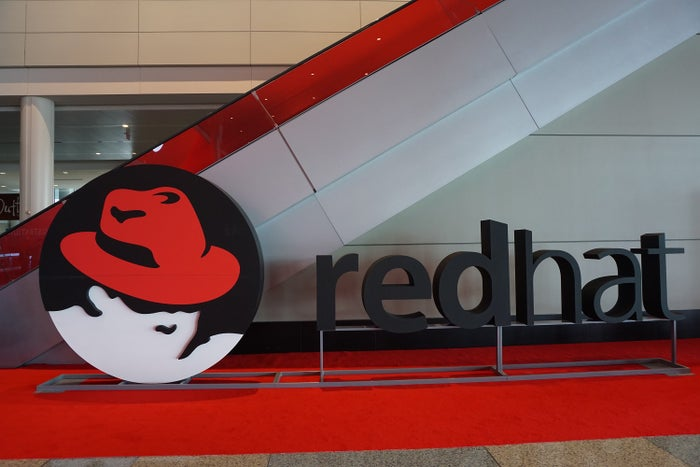 Red Hat logo in front of a staircase going up.