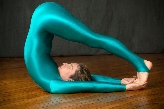 Contemporary young woman dancer with short hair, wearing a blue unitard body suit while lying on the wood floor of the studio with her legs bent back over her head.