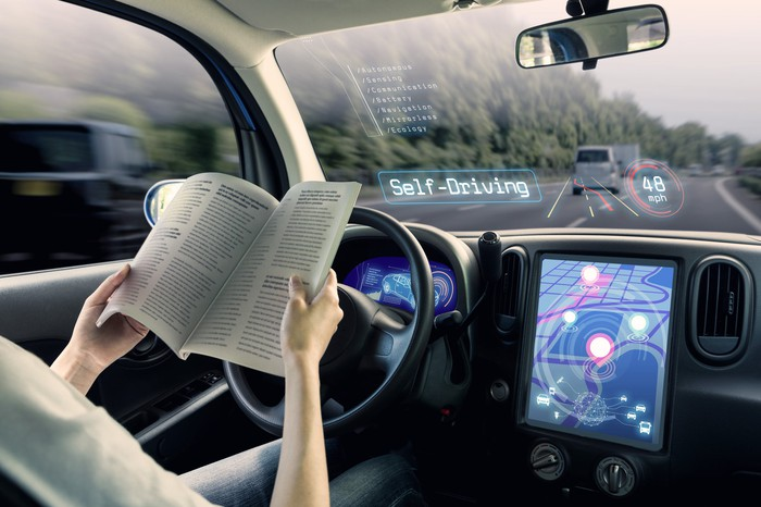 """animation showing driver reading a book in driver's seat as car drives itself. The words """"self-driving"""" appear ont he windshield."""