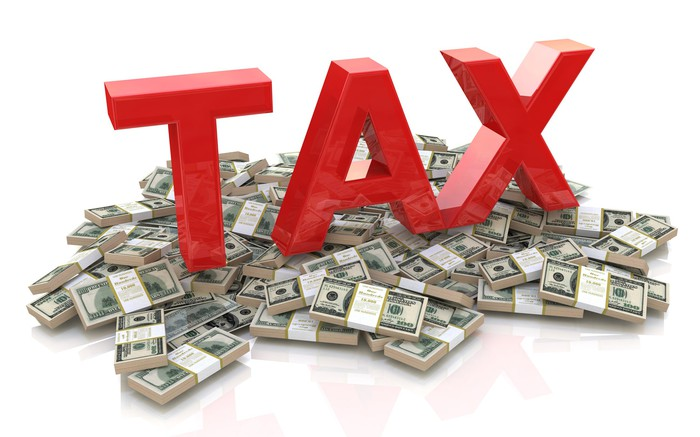 The word tax is spelled out in capital letters atop of a pile of banded paper currency.