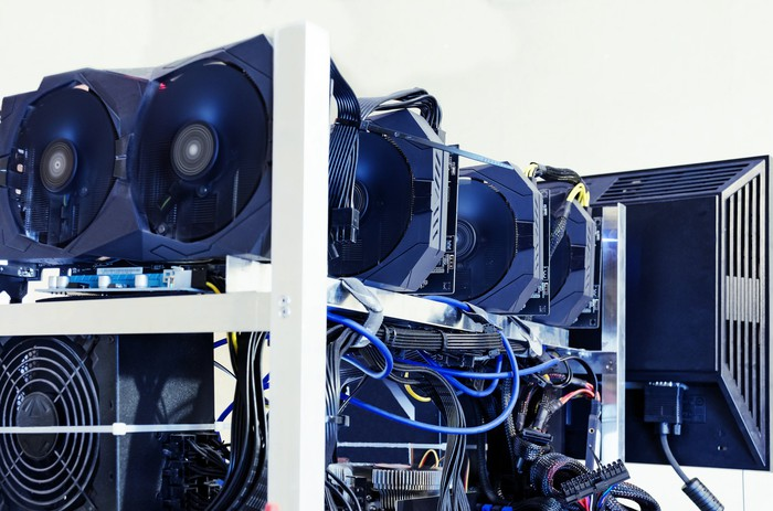 Hard drives and graphics cards, along with a monitor, used for cryptocurrency mining.