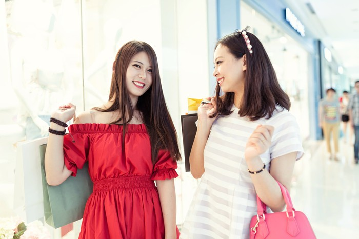 Two young women smiling while shopping at a mall.