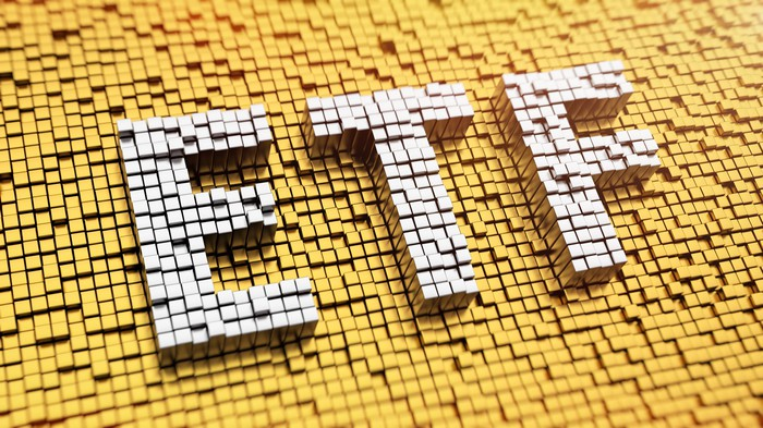 Letters ETF spelled out in white mosaic tiles on a yellow mosaic tile background.