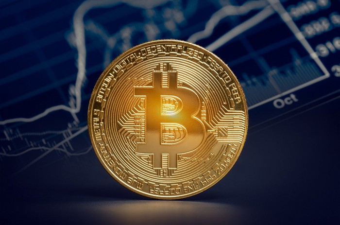 Gold metal circle with bitcoin symbol engraved on it, in front of pictures of charts.