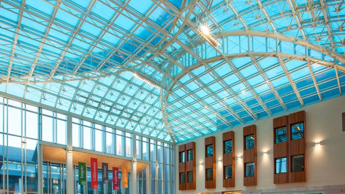 Blue glass ceiling with metal framing over a wide-open lobby space.