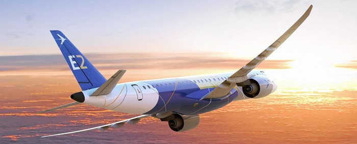 Embraer E2 jet, airborne flying toard a rising or setting sun with few clouds below.
