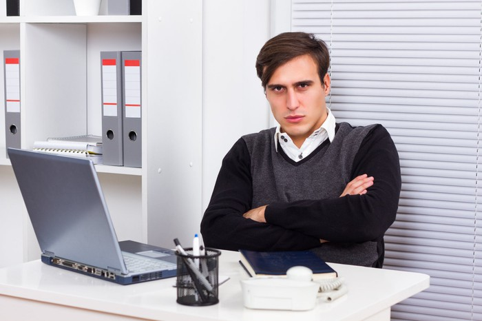 An angry young man with his arms crossed while seated at his desk in front of his laptop.