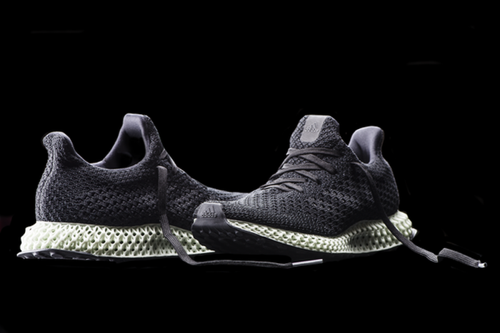 A pair of adidas' Futurecraft 4D running shoes -- dark-colored uppers, light-colored and lattice-shaped midsoles, with a black background.