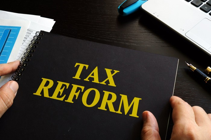 Two hands hold a black notebook on a desk, with the words tax reform printed in yellow on the cover.