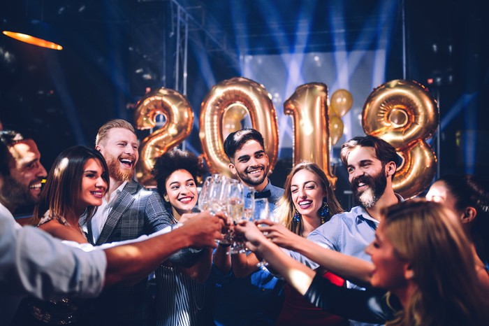 A group of young people toasting with champagne glasses, with a 2018 balloon in the background