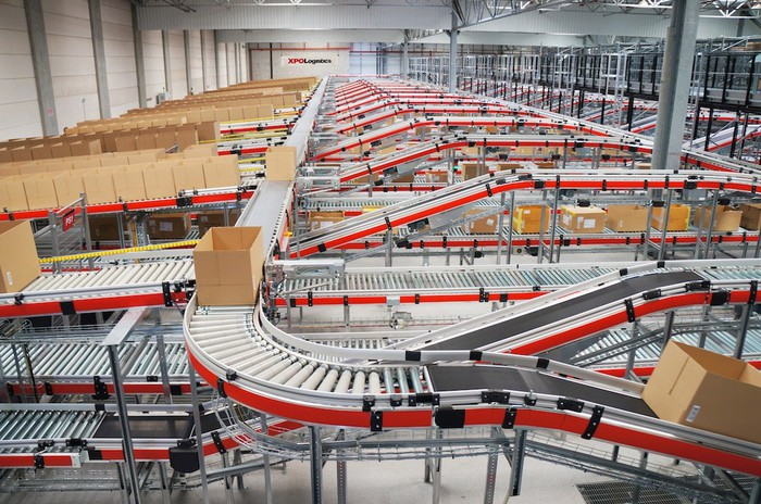 Boxes move on a series of conveyor belts inside a warehouse.