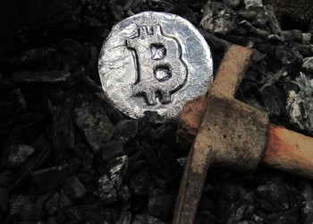 pickaxe and silver coin with bitcoin symbol on it lying on a pile of coal -- bitcoin mining cryptocurrency