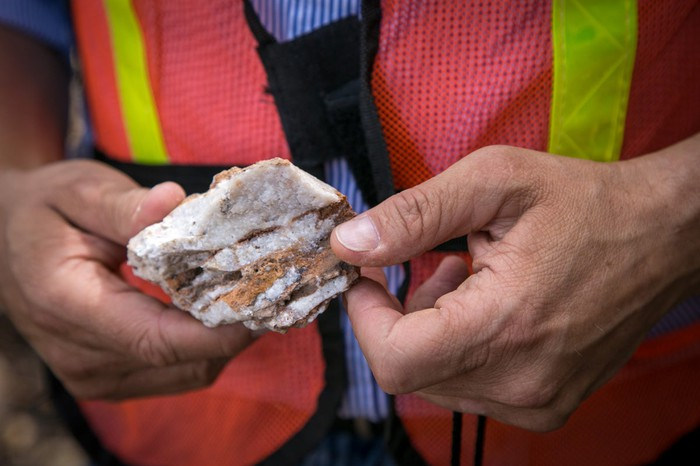 Person in safety vest holding a piece of silver ore in hand.