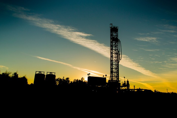 Drilling rig at sunrise on a clear day, with equipment nearby.