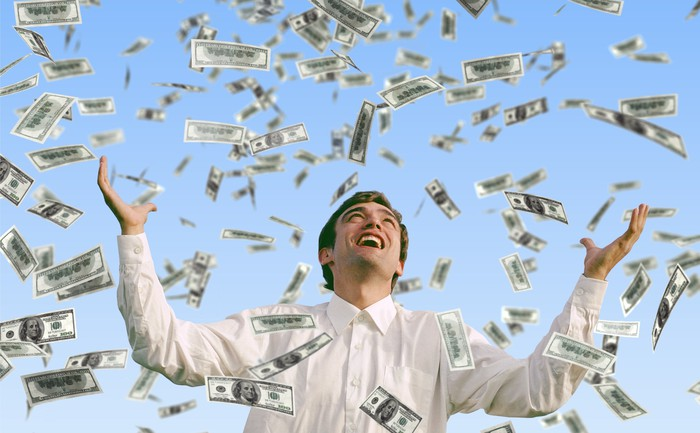A man stands in a shower of cash.