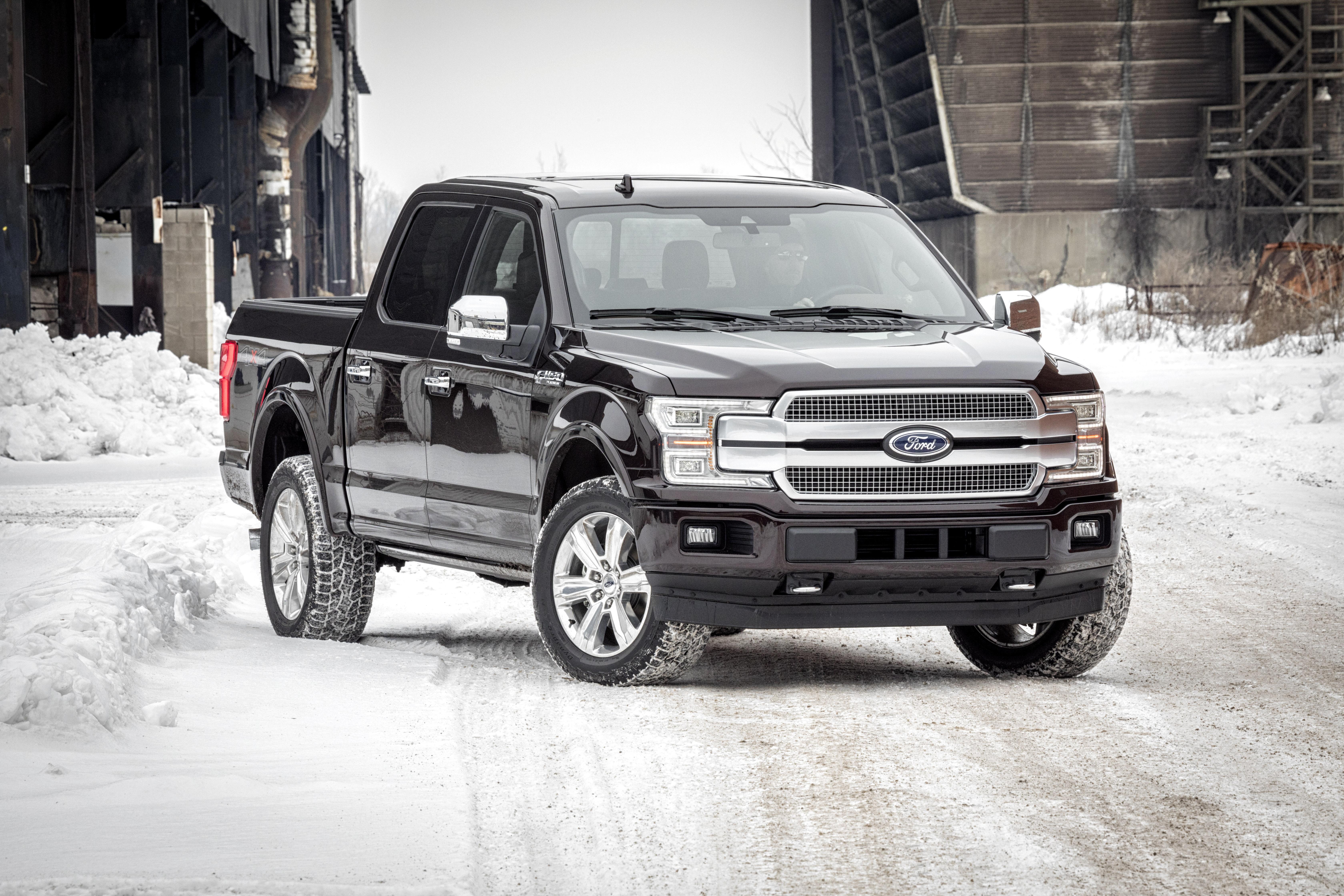 A black 2018 Ford F-150 pickup truck on a snowy street.
