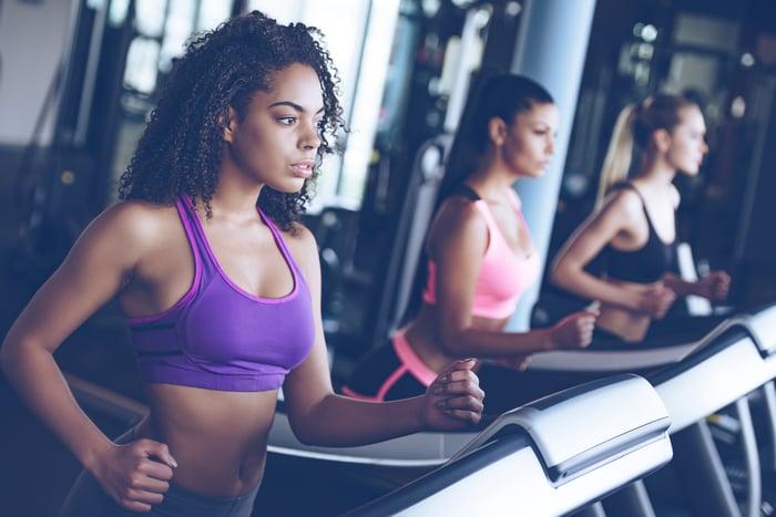 Three women in exercise clothing running on treadmills.