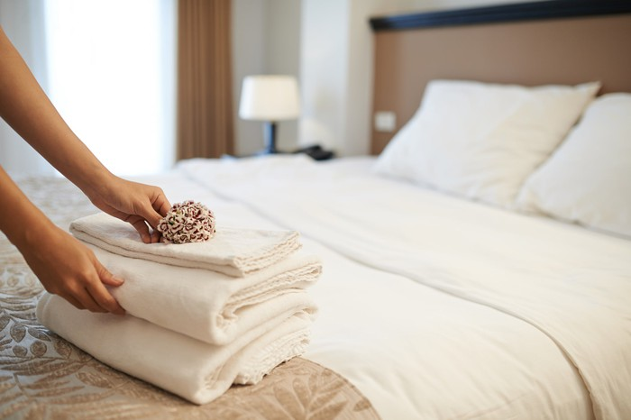 Person setting out towels on bed