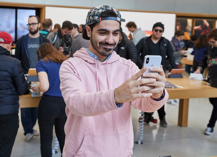 A person holding an iPhone X inside of an Apple store.