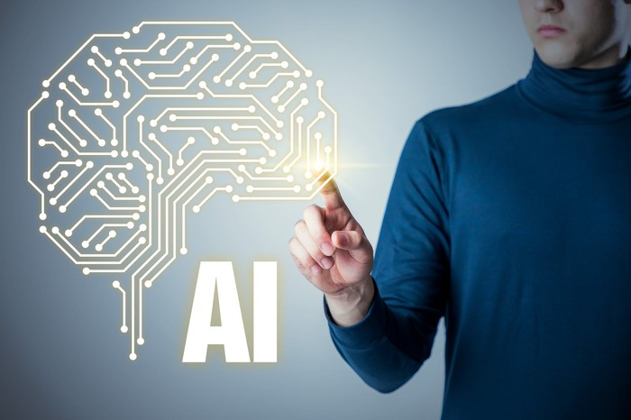 "A person in a blue turtleneck pointing to a screen with an image of digital human brain and the letters ""AI."""