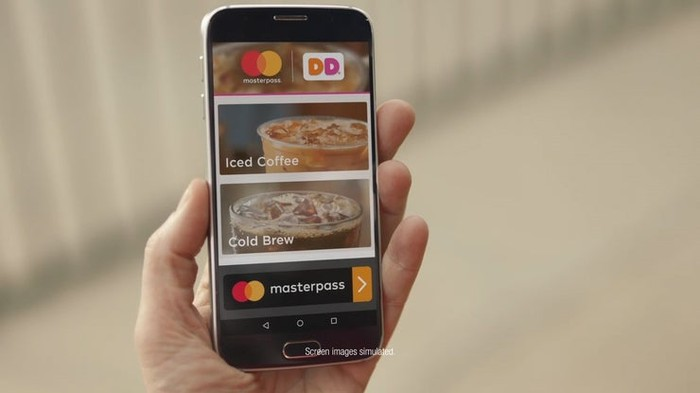 Hand holding mobile device displaying Mastercard's Masterpass and Dunkin' Donuts logos, along with mobile menu coffee images.