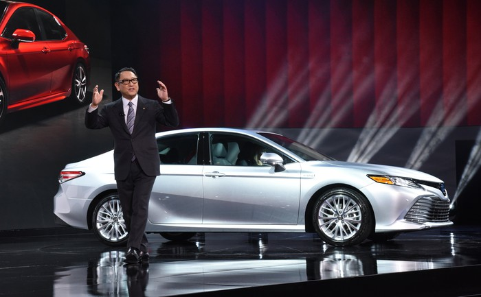 Toyota CEO Akio Toyoda is on stage with an all-new 2018 Toyota Camry sedan behind him.