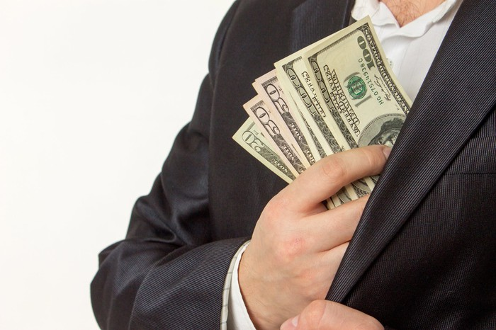 A businessman putting a stack of cash into his inner coat pocket.