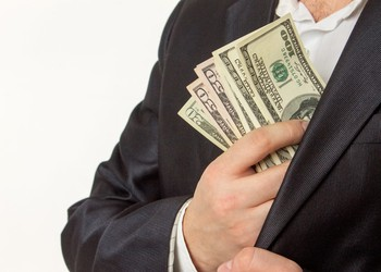 Businessman Putting Money in Jacket Pocket Dividend Getty